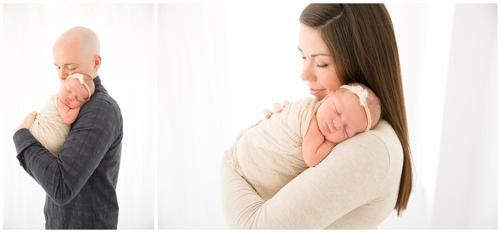 mom and dad snuggling their newborn baby girl for her baby photos in burlington new jersey