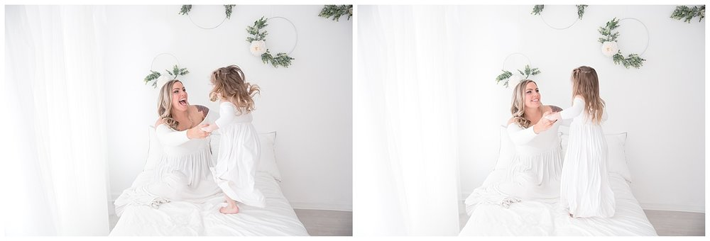 four year old jumping in bed wearing a white dress