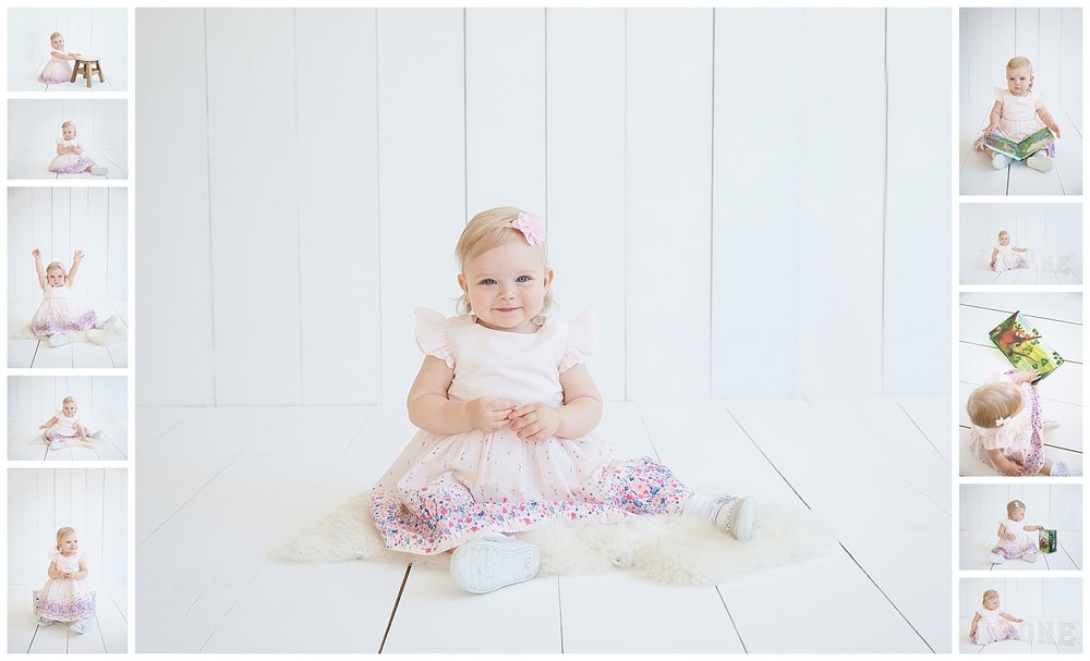 little girl wearing a white dress in a white studio in moorestown new jersey reading a book and smiling