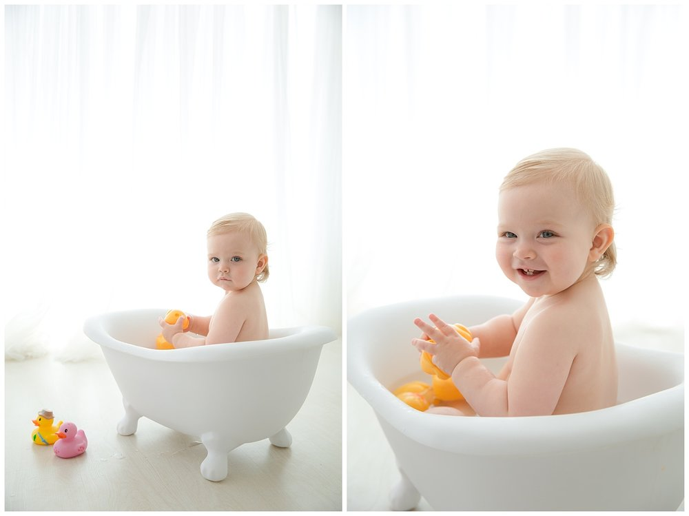 one year old girl splashing in white claw foot tub in moorestown new jersey studio