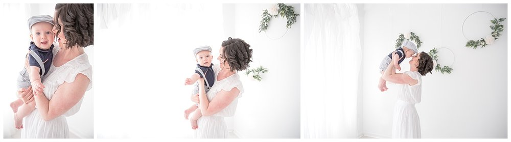 mom wearing a white dress with her son in a blue hat for mommy and me session in moorestown new jersey studio