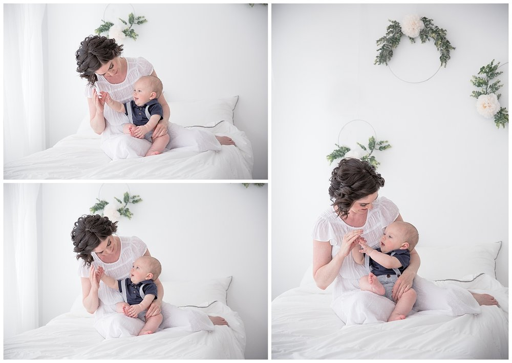 mom playing hand puppets with son while wearing a white dress and son in a blue shirt on a white bed in burlington new jersey studio