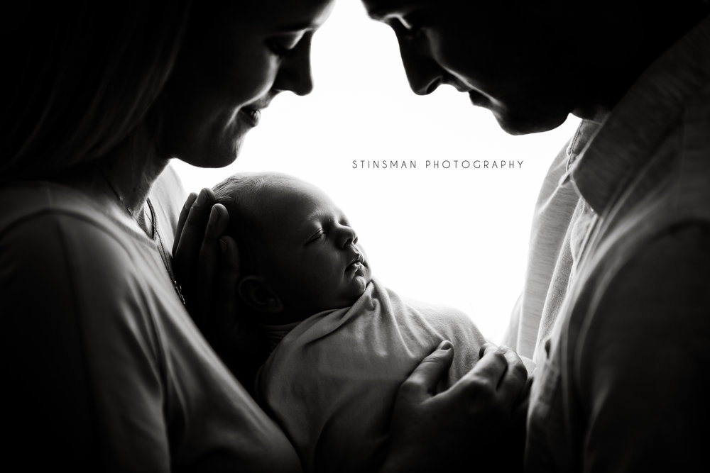 black and white timeless photo of mom and dad holding their son in burlington new jersey studio