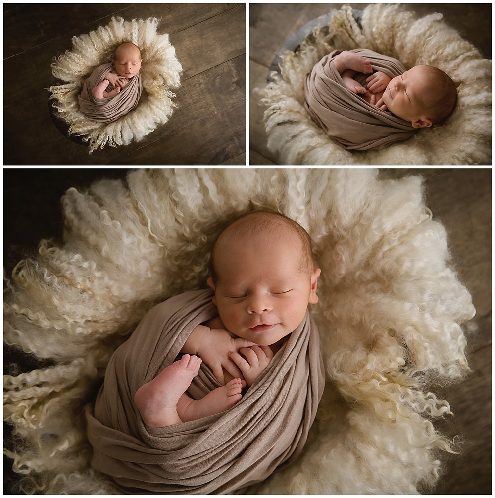 14 day old baby boy smiling while wrapped in brown on dark brown wood in burlington new jersey studio moorestown