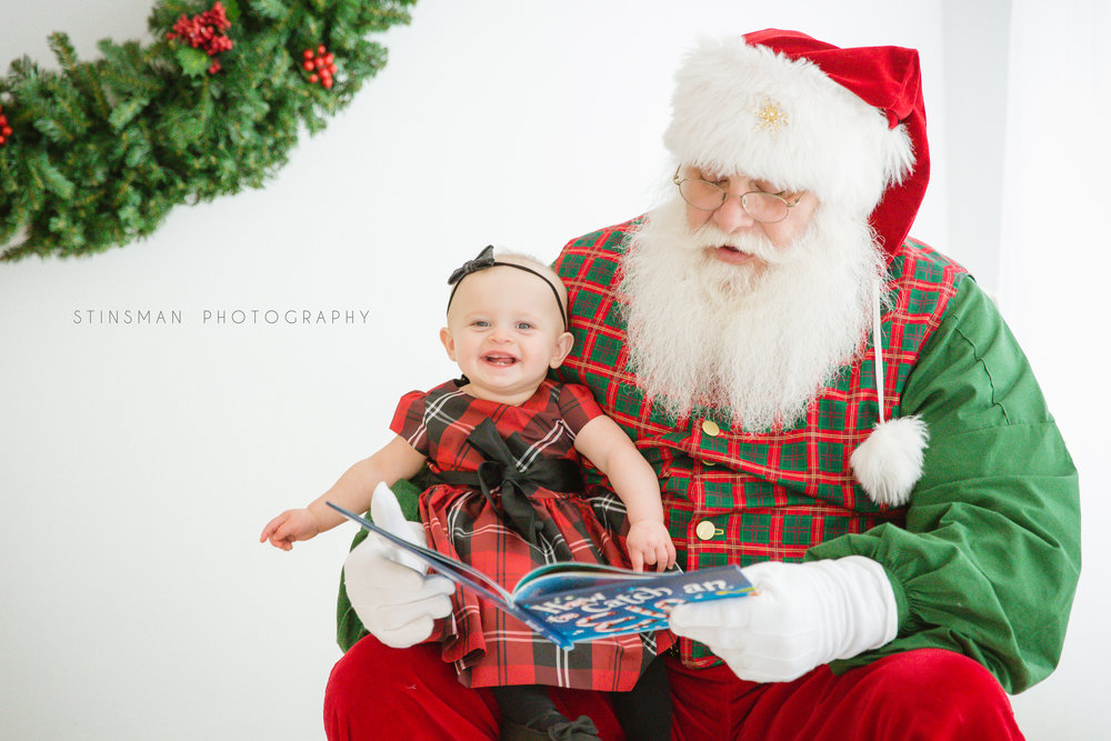 baby girl named molly smiling with santa while he reads her a funny story in burlington nj photo studio