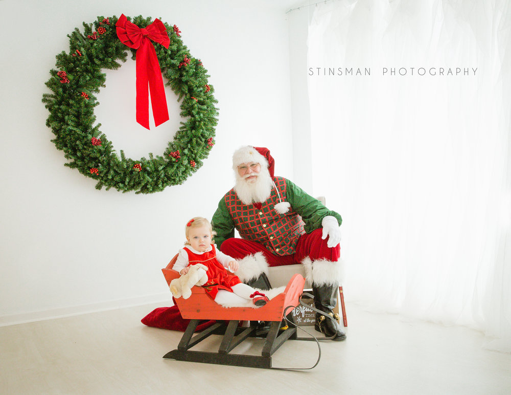 little girl sitting in a sleigh with santa for photos in burlington nj photo studio