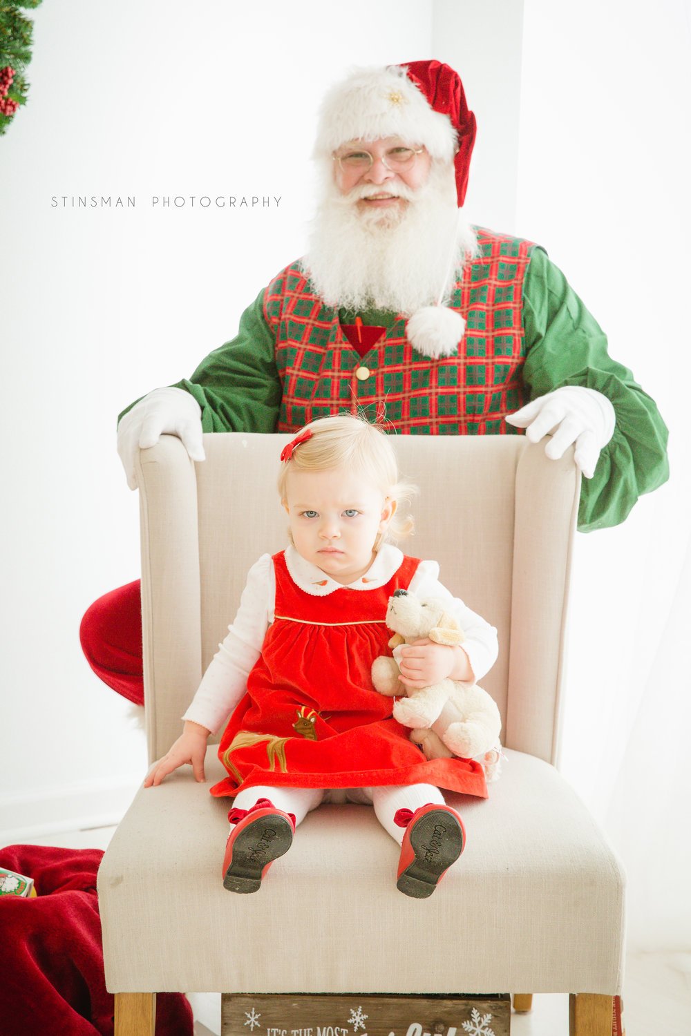 little girl sitting in a chair with Santa behind her in burlington nj photo studio