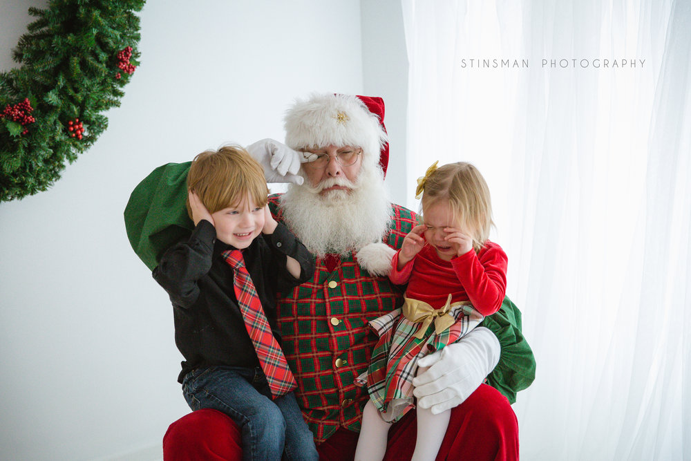 little girl crying while seeing Santa and brother holding his ears in burlington new jersey photo studio