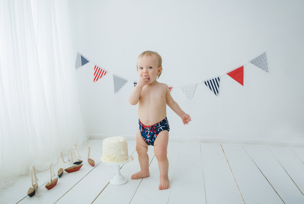 little boy with a nautical cake smash theme eating his cake in burlington nj photo studio