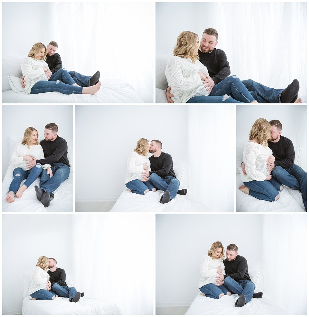 Mom and dad cuddling in Burlington nj photo studio for maternity photos wearing a white sweater in a white bed.