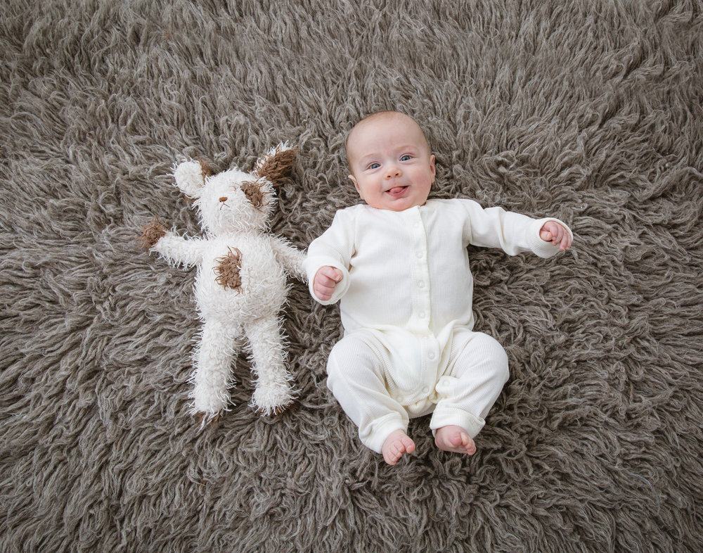 baby-boy-wearing-white-on-a-grey-rug-with-his-favorite-toy.jpeg