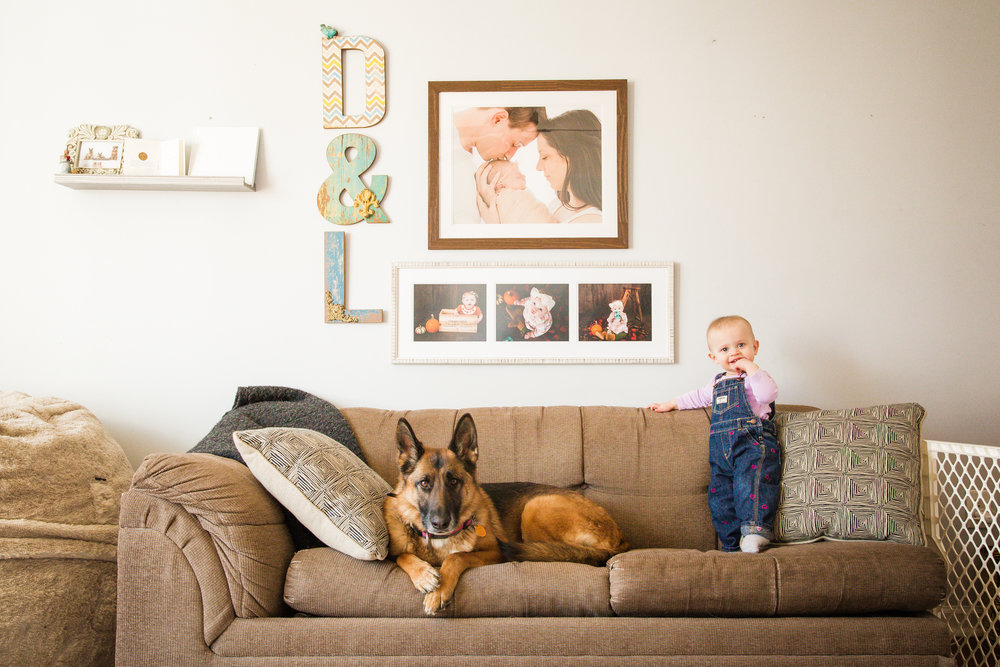 baby girl on the couch with photos on the wall of her