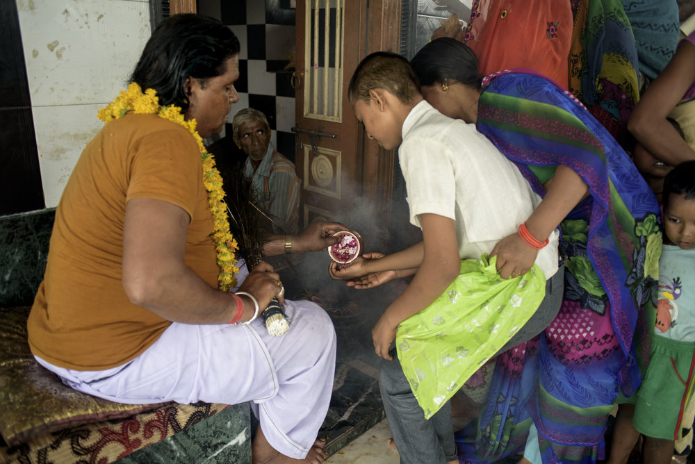 A young boy takes the blessings of the head Bhopa. The people come in thousands to perform weekly rituals and offer a sum of money, fruits, garlands. People wait in a long queue to meet the head Bhopa and taste the holy water given by him.