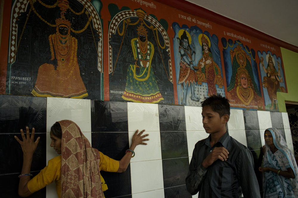 A woman touches the walls of the temple that is commonly known as Kupra Maata Ka Mandir, situated 5 kilometres from Banswara town. The villagers hold immense faith in healing through ceremonies that take place in the temple compound every weekend.