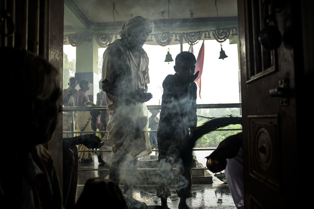 Smoke from burning a bundle of incense sticks fills up spaces within the temple, while people await their turn to meet the head Bhopa.