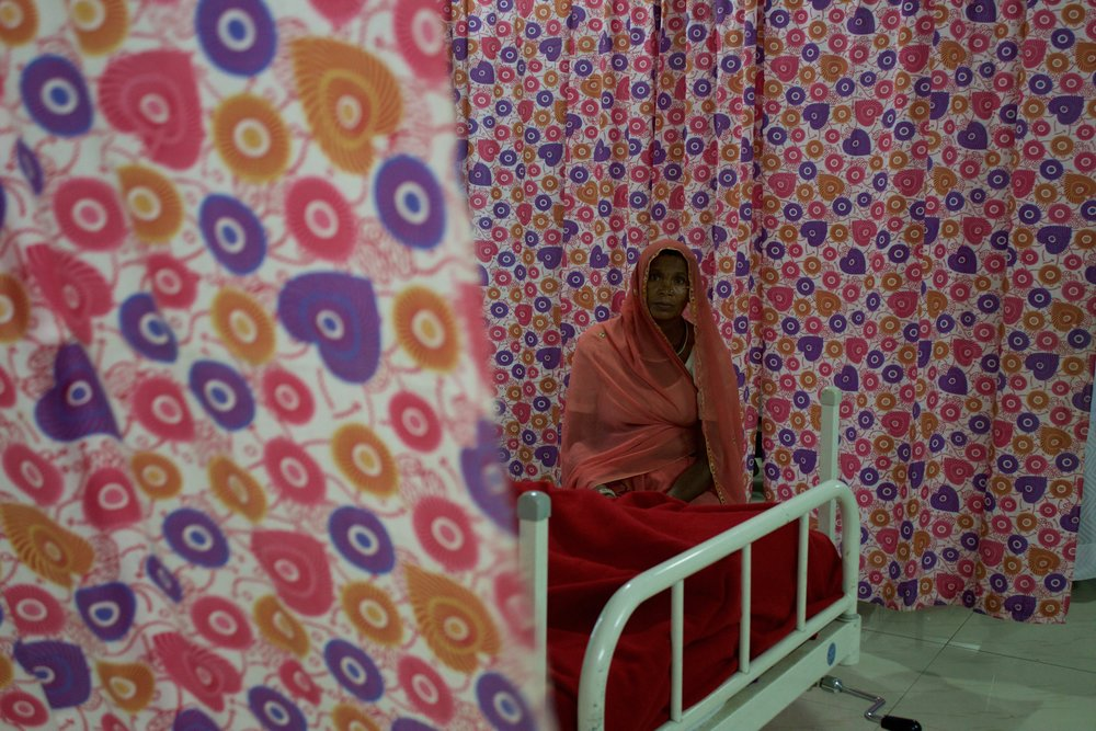 A mother sits by the bedside of her daughter who is being treated, at no cost, for hemorrhaging in the Intensive Care Unit of Zanana Hospital.