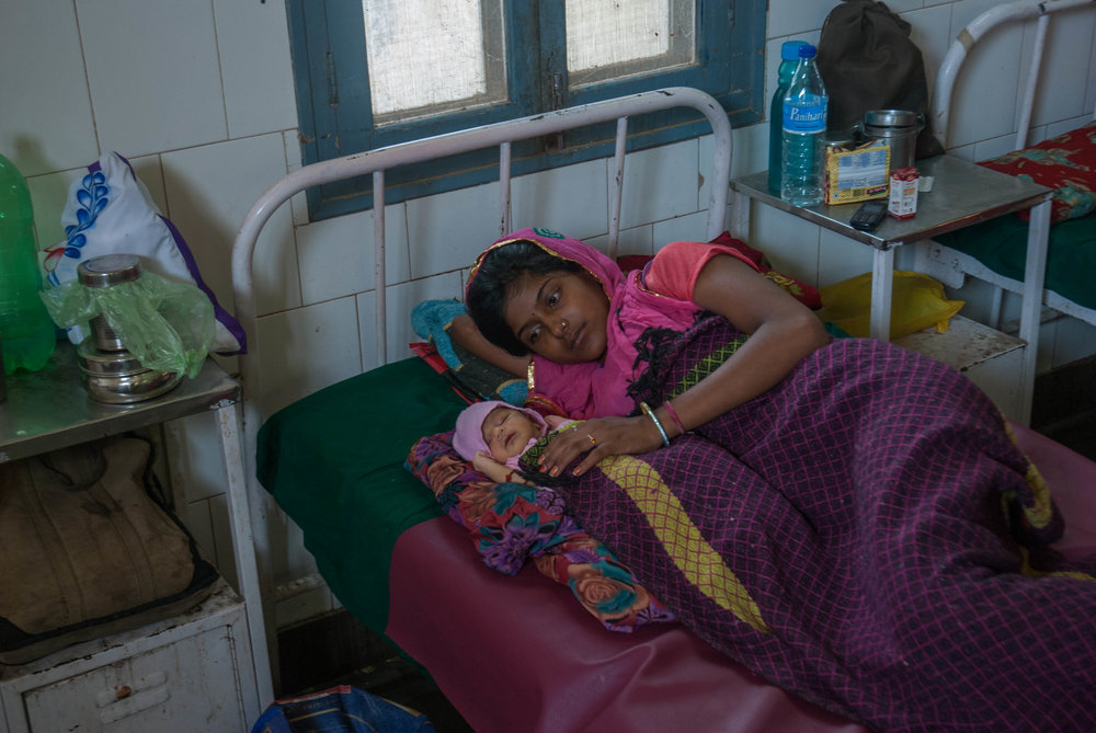 In the maternity ward, a 19-year old mother lies in bed with her daughter.