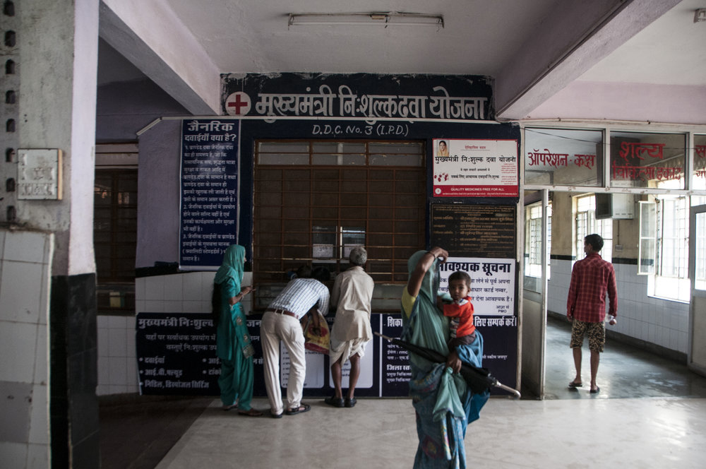 Patients outside the District Drug Center (DDC) No.3 of Chittorgarh's District Hospital on a day of unusual calmness, after days of flash floods. This hospital houses 8 DDCs, and multiple Lifeline counters where patients can obtain generic medications that are not on the Essential Drug List of over 500 items.