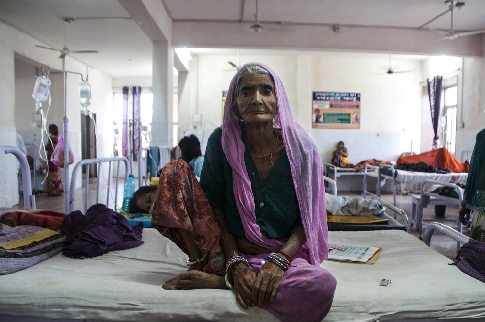 Mangi says that she's probably older than 70 and complains of pain in her lower abdominal area. Her sonogram report says she is 60, and has gross ascitis. She's been coming to Chittorgarh District Hospital for around three years to seek treatment and the scheme covers all her medication. She says that the scheme has been the most helpful for chronic patients.