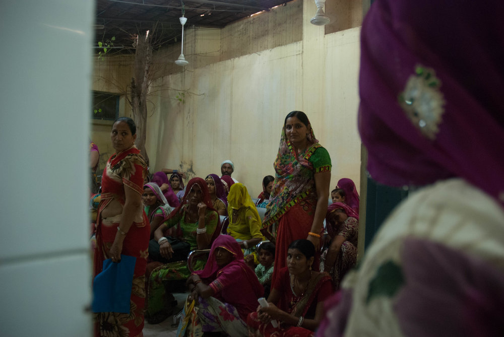 Medical patients crowd into a room, waiting to be called to retrieve their blood test results at the District Hospital, Bikaner.