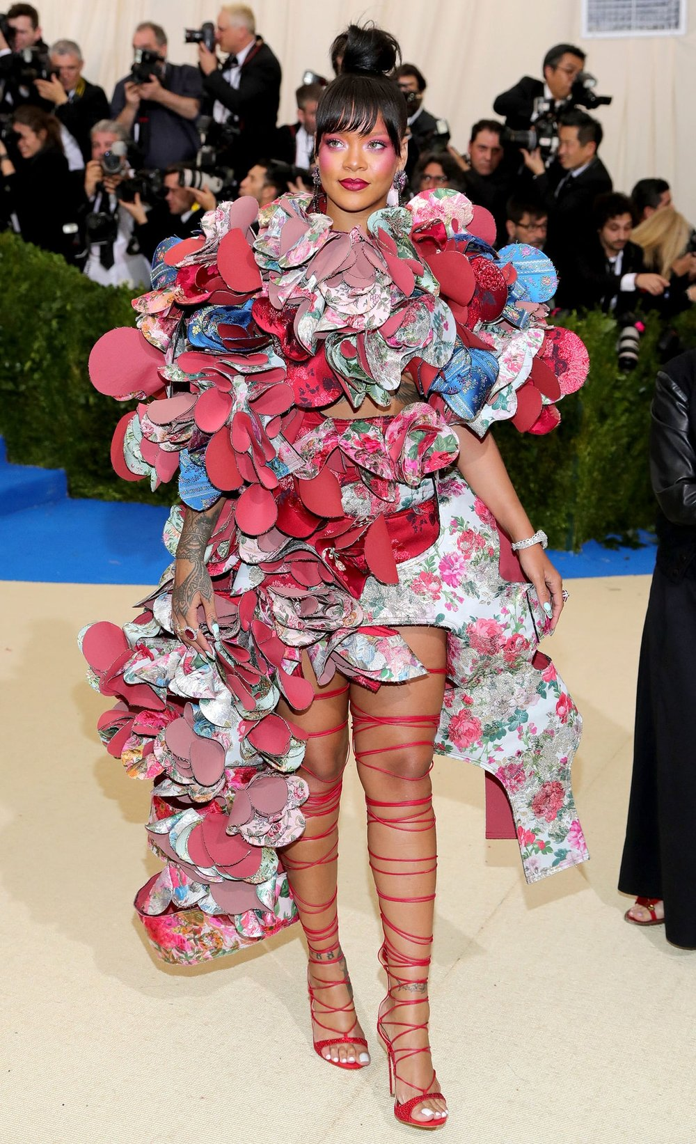 Rihanna   in Comme des Garçons . Nobody can understand this look including me who will literally love a potato sack if she throws it on. I'm not sure if it's the Geisha vibe, the pink highlighter, the multicolored petals or the electrical wire heels that are making me cringe? I think it's all of it.