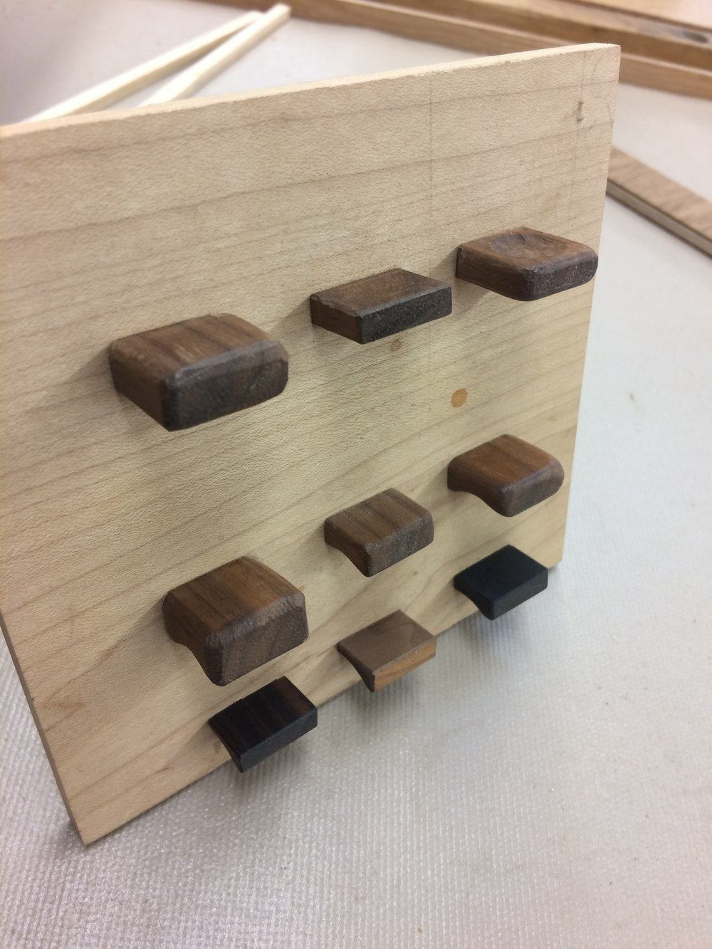 Walnut and ebony pull prototypes. The upper row has hand carved dimples underneath as a little tactile surprise. I think I will go with something from the bottom row, however. The cabinet is brutal in form and a pull that is similarly planar will fit its gestalt.