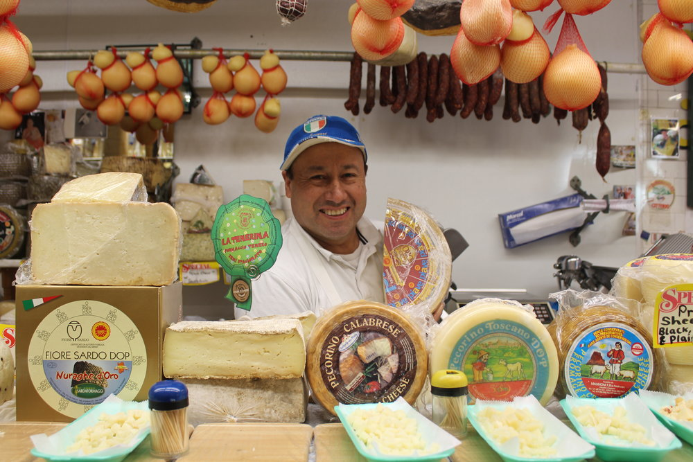Diego behind the counter of Calandra's Cheese at 2314 Arthur Avenue