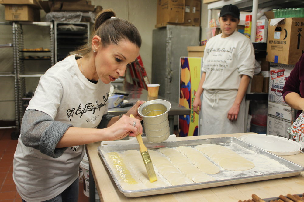 Cookbook author  Tina Ruggiero  paints with egg wash, crucial to keeping the cannoli shells closed when they go in the deep fryer. Aura, one of Egidio's bakers, assisted our guests.