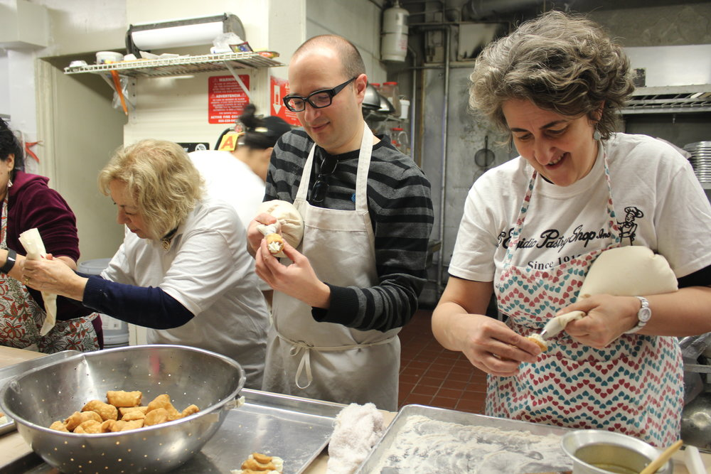 Greg Dolin and Francesca Burns get the hang of filling cannoli