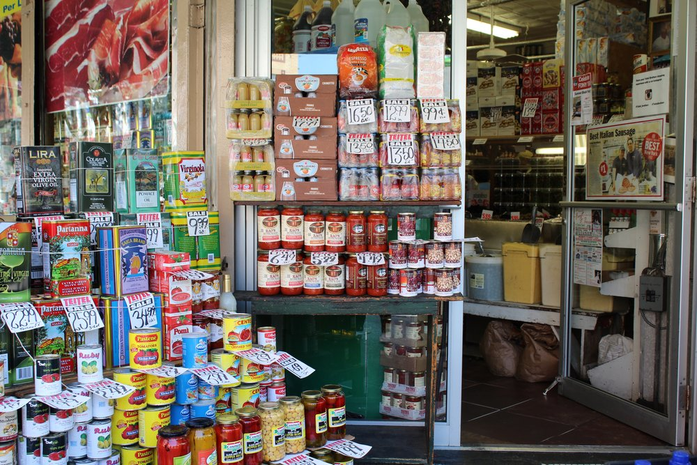 Olive oil, tomatoes and other canned goods stacked in front of Teitel Brothers.