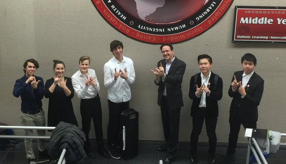 "Members of the Chamber Ensemble form the La Lumiere ""LL"" symbol with their hands after earning a gold rating at the ISSMA State Solo and Ensemble contest in Indianapolis on February 23, 2019. (Left to right: Oliver Gnaedinger '21, Brenna Hudson '20, Quentin Funderburg '21, Nicholas Gnaedinger '19, Brad Poore, Music Director, Hongkai ""Donny"" Lou '20, Dingwei ""Martin"" Ma '22)"