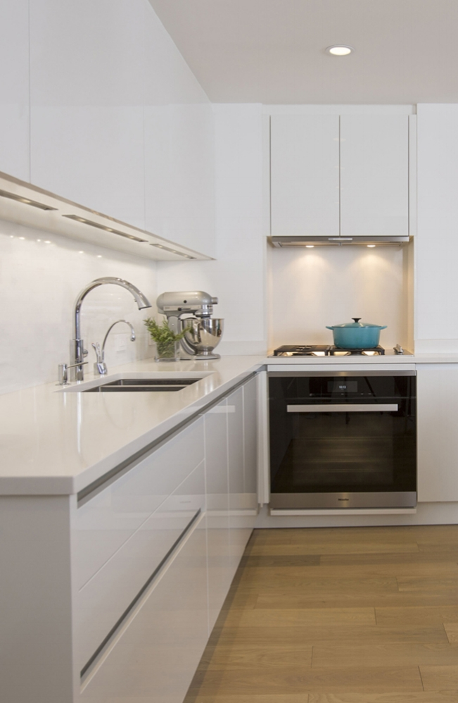 GLOSSY WHITE KITCHEN, including semi-custom cabinetry, Caesarstone counters and and a natural stone backsplash.