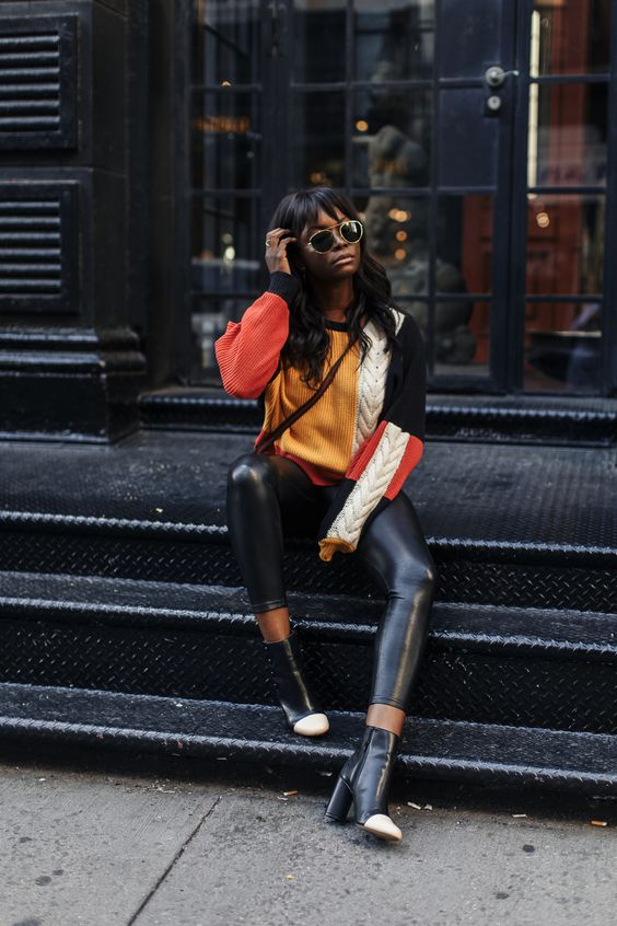 Love how    Coco Bassey    paired her color block sweater with leather leggings. The cap toe boots are fun too.