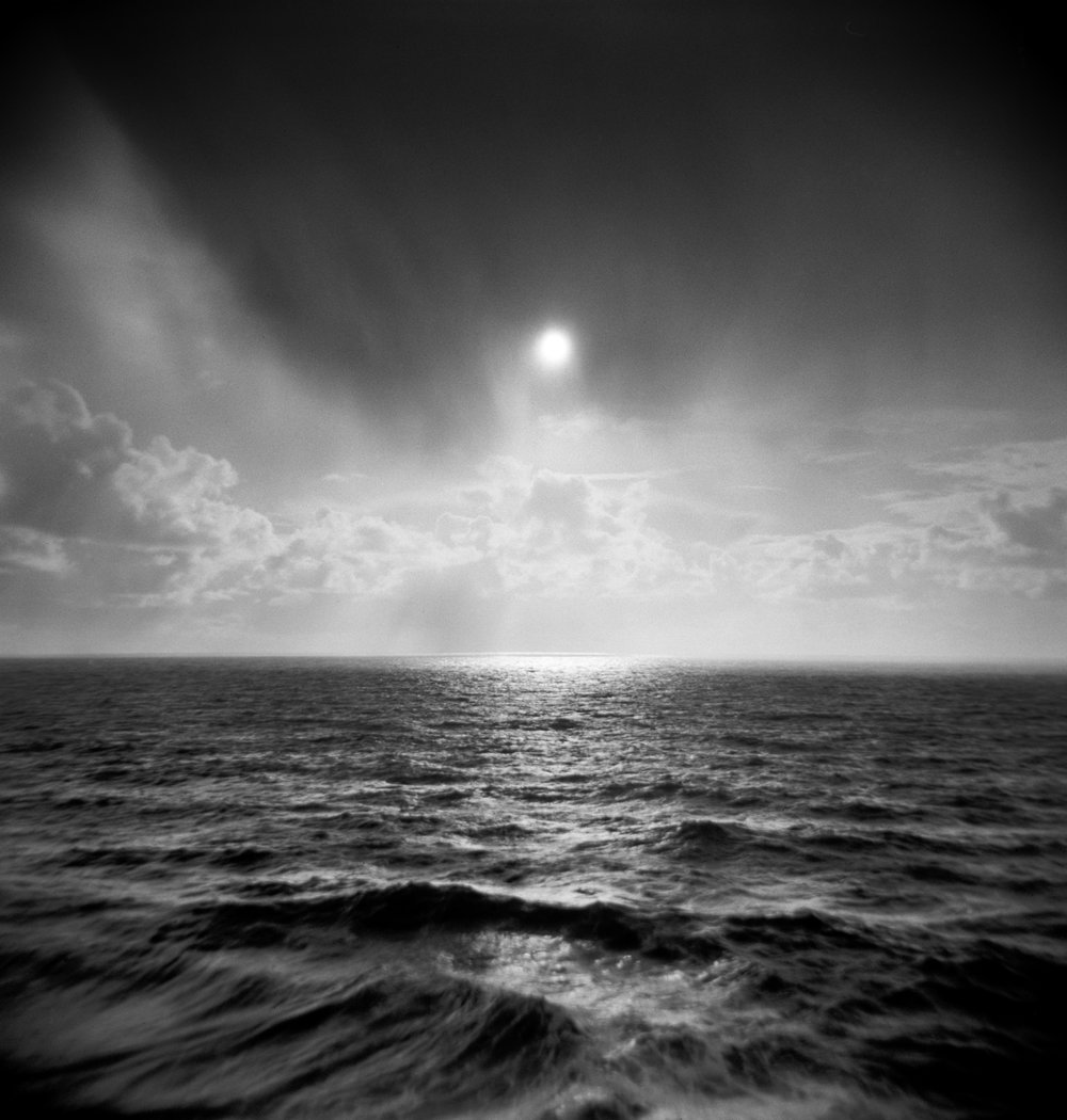 Sun through clouds over ocean holga.jpg