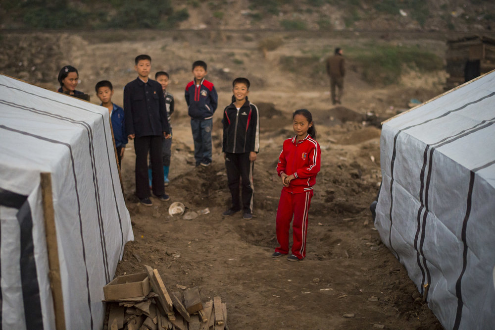 Children stand where their homes once stood in Musan County.
