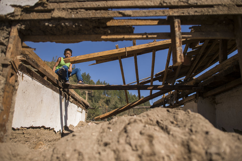 A child sits in the ruins of his home in Yonsa County.