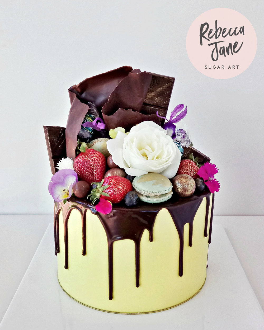 Rebecca Jane Sugar Art - yellow drip cake with chocolate sail, berries, macarons and flowers