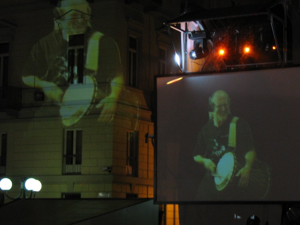 Ian Playing Talking Drum. Projection in Torino, Italy During Olympics.