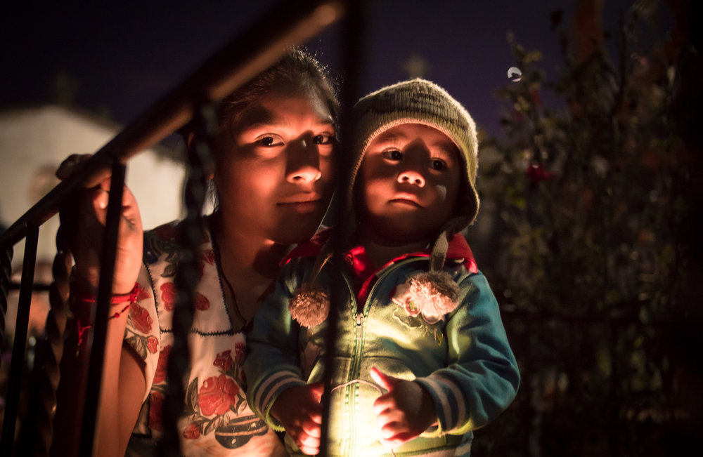 A mother and her son during Day of the Dead. Native Purepechas inhabit the island and celebrate the lives of their deceased loved ones here.