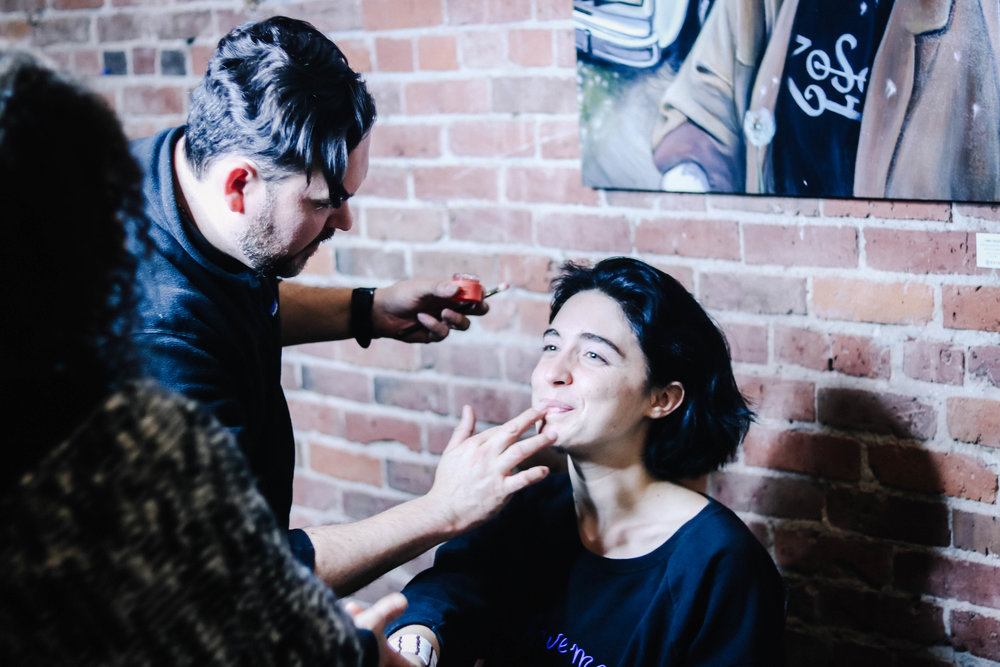 Makeup artist Leo applies foundation on event producer Ava Holmes (wearing Fashion for Conservation NO VOICE hoodie).
