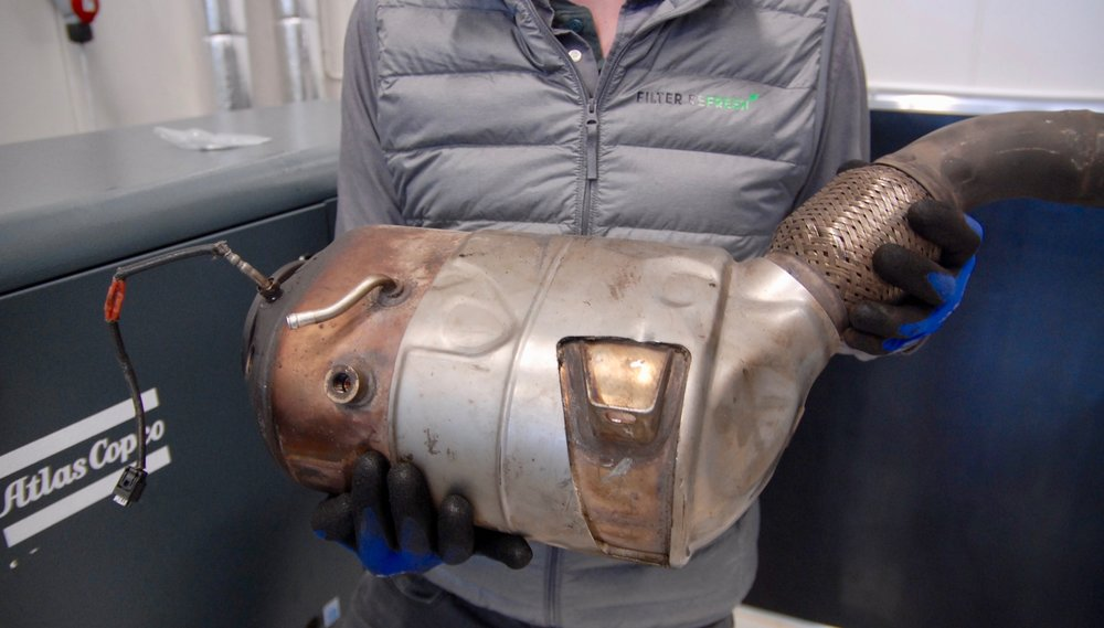 En av Filter Refreshs tekniker med ett partikelfilter till en BMW före inspektion och rengöring.