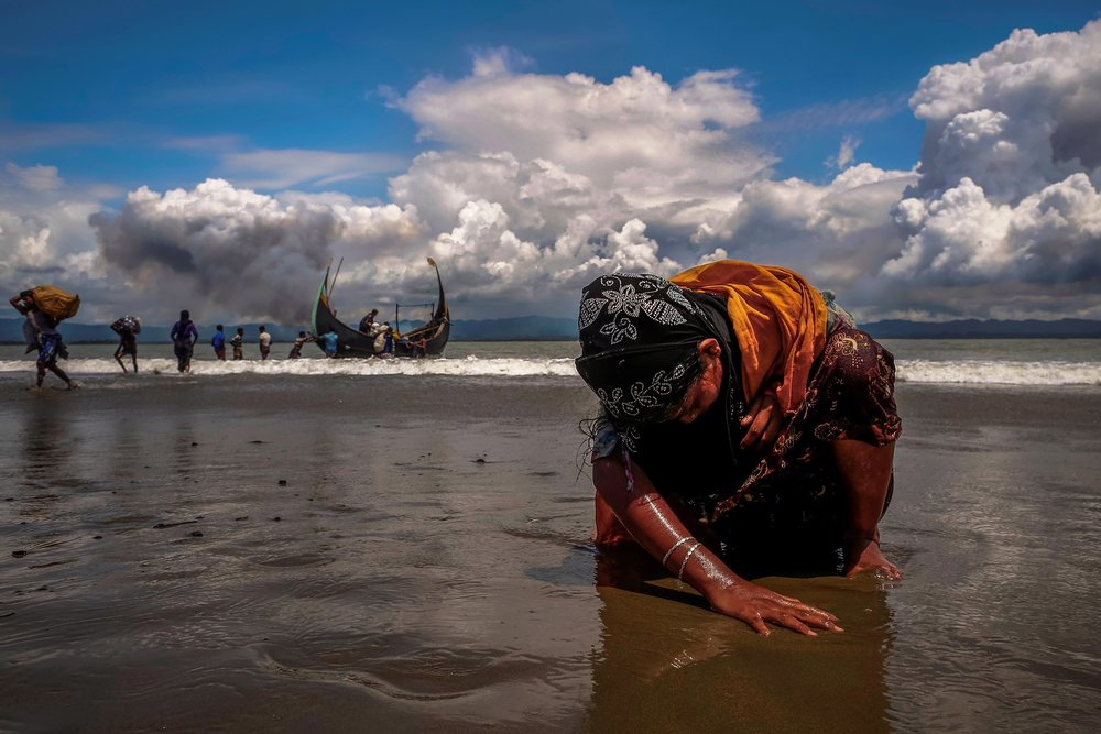 Image caption - An exhausted Rohingya refugee woman touches the shore after crossing the Bangladesh-Myanmar border by boat through the Bay of Bengal, in Shah Porir Dwip, Bangladesh September 11, 2017.   Credit - REUTERS/Danish Siddiqui