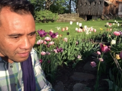 CLA founder Arn Chorn-Pond in front of the tulip garden