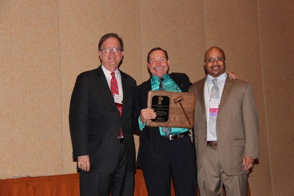 Passing the gavel, Dr. Kevin Williams (right) presents Dr. Rick Grant with the Gavel of Office, a plaque recognizing Dr. Grant's achievements as IAO President in 2013-2014.