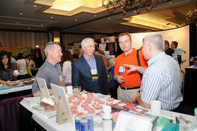 Dr. Brock Rondeau (second from left) and IAO Poland Section representatives, Dr. Marcin Dolecki (orange shirt) and Mr. Romuald Ciesielski (right) interact with Randy Williams (far left) from Dyna Flex.