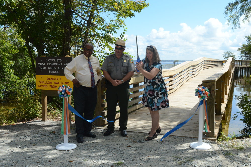 Dwayne Patterson of DEHNR joins Toby Hall of the Lake Waccamaw State Park and Hannah Cockburn of the DOT to cut the ribbon on the Lake pedestrian bridge.