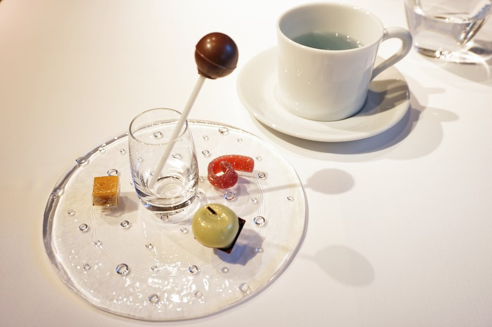 """Nibbles for chat"":  Petit fours and tea: Passion fruit jelly candy, dark chocolate with green apple puree, plum soft candy, chocolate lollipop with popping candy."