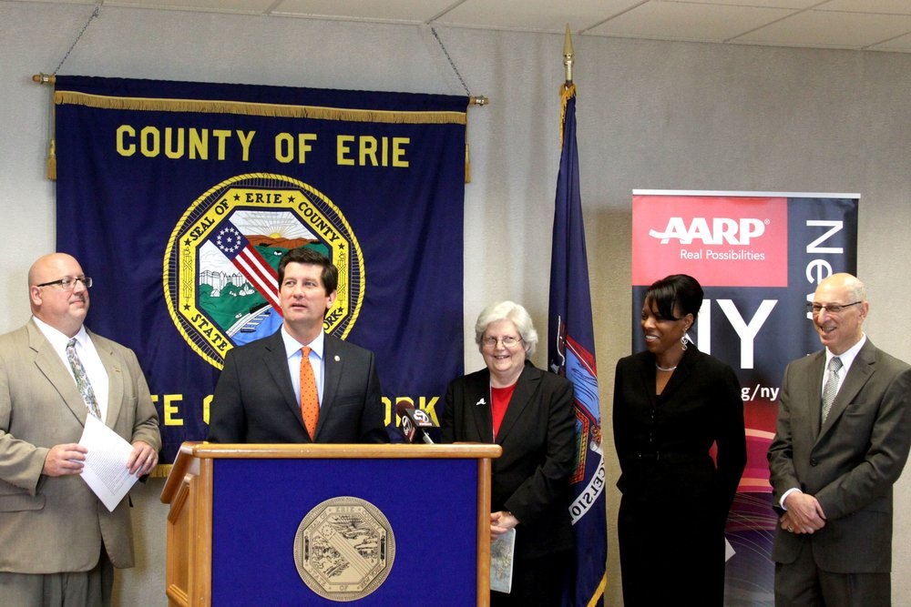"AARP Associate NYS Director for WNY Bill Armbruster, Erie County Executive Mark C. Poloncarz (at podium), AARP State & National Group Executive Vice President Nancy LeaMond, Director of the NYS Office for the Aging Corinda Crossdale, and UB IDeA Center Director Dr. Edward Steinfield at Monday's announcement recognizing Erie County as an ""Age Friendly Community"".  CREDIT ERIE COUNTY"
