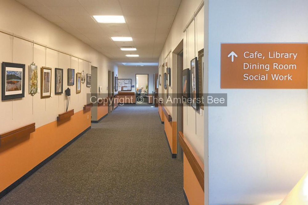 An orange sign in the Amherst Center for Senior Services hangs in front of a corridor to indicate which rooms and services are ahead. (The Amherst Bee)