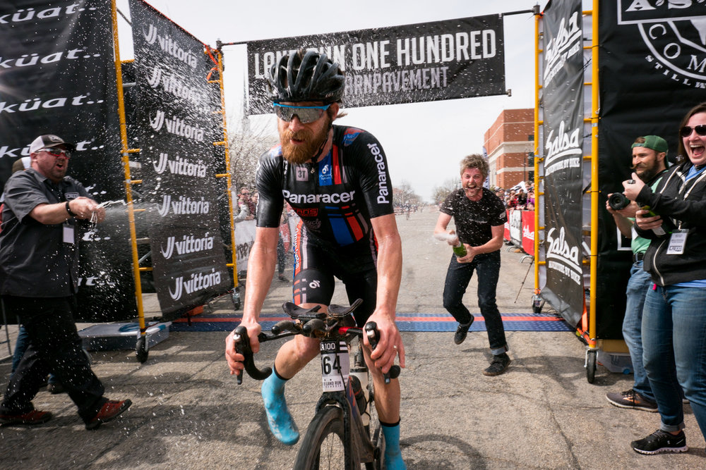 2018 winner Mat Stephens crosses the finish line in a champagne blitz